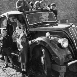 Small children ( at least 10!) pose with an old car that has been donated to their school for them to play with.