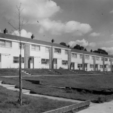 Terraced houses with an open grass area in front and footpaths but no access for cars.