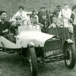 Boys and their families crowd around an old banger.